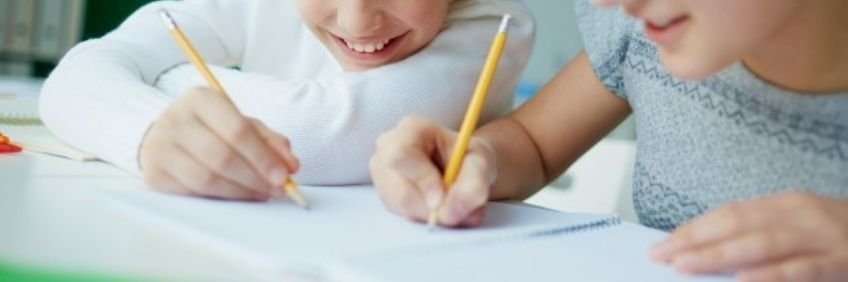 Dos niños escriben a lápiz en un cuaderno. Consejos y actividades para escribir buenos diálogos.