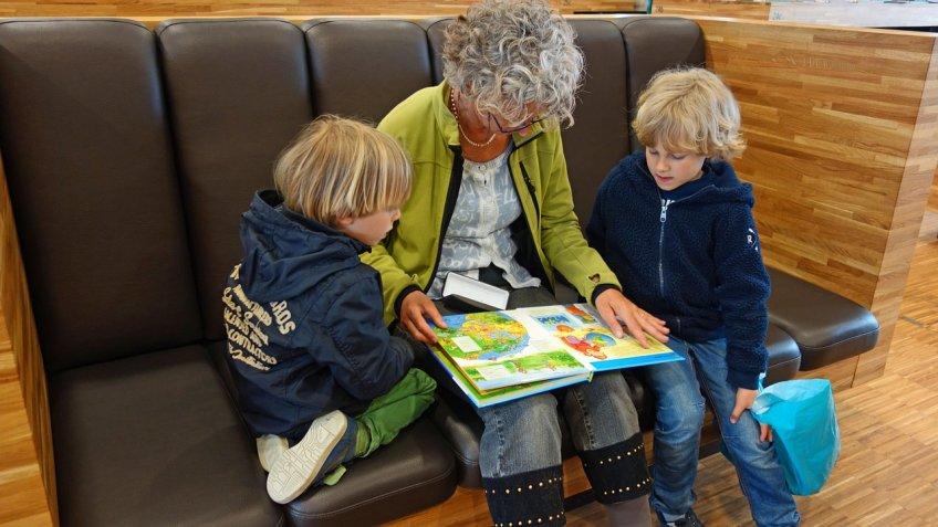 Abuela leyendo a nietos en el sofá