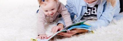 Bebé con su madre con un libro de tacto. 10 beneficios de la cuentoterapia para los niños