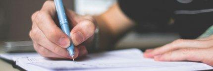 Chico escribiendo una redacción en un cuaderno. Decálogo para una buena redacción de Literatura SM.