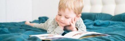 Niño pequeño leyendo un libro infantil en la cama. Libros infantiles para la psicomotricidad fina