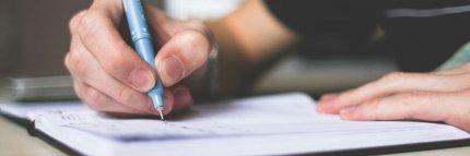 Un adolescente escribe en un cuaderno. Cómo desarrollar la trama de tu historia por Literatura SM.